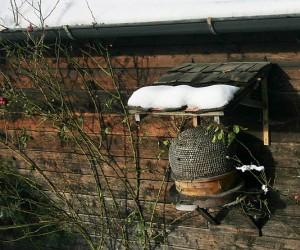 Salzburgerland : ruche-panier traditionnelle accrochée en hauteur au mur d'une vieille ferme sous l'auvent qui la protège de la pluie et de la neige